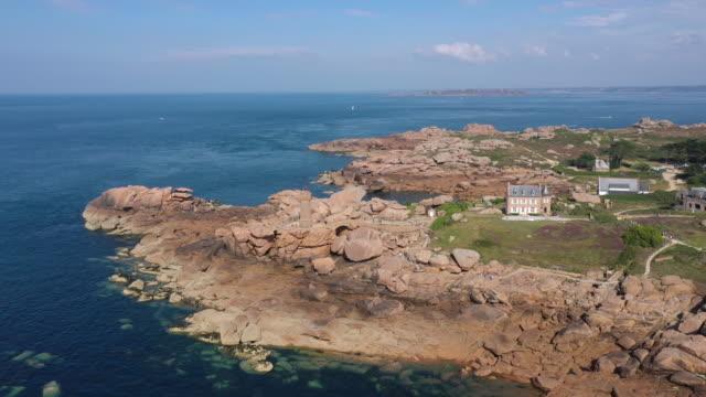 vidéos et rushes de aerial view of the coastline in cote de granit rose around lannion, red cliff rocks at sunset, brittany, france - granit