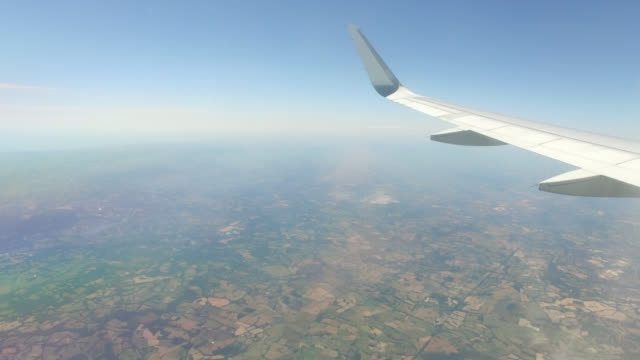 vidéos et rushes de aerial view of the countryside in england with the sea, aircraft wing - patchwork landscape