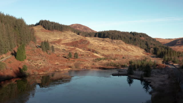 aerial view of the edge of a scottish loch in dumfries and galloway on a bright autumn morning - johnfscott stock videos & royalty-free footage