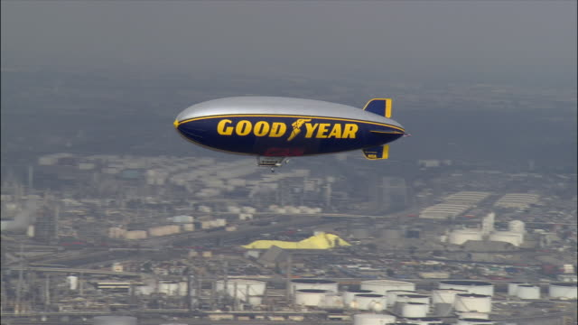 Aerial view of the Goodyear Blimp sailing over city / Long Beach, California