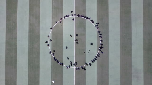 aerial view of the graduation students showing different pattern in the soccer field - circle stock videos & royalty-free footage