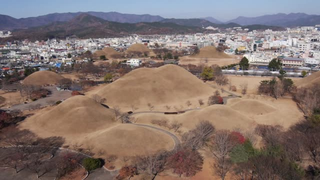 aerial view of the hwangnam daechong (great tomb of hwangnam during the silla kingdom) and the city in gyeongju - gyeongju stock videos and b-roll footage