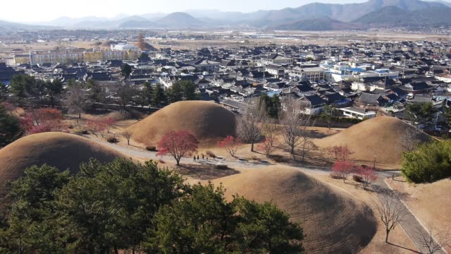 aerial view of the hwangnam daechong (great tomb of hwangnam during the silla kingdom) and the traditional village in gyeongju - gyeongju stock videos and b-roll footage