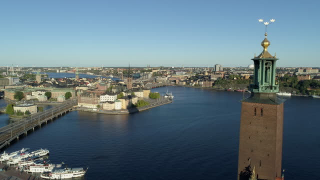 aerial view of the landmark the city hall in stockholm and its three crowns on kungsholmen with gamla stan, the old town,and sodermalm in the background. - tornspira bildbanksvideor och videomaterial från bakom kulisserna