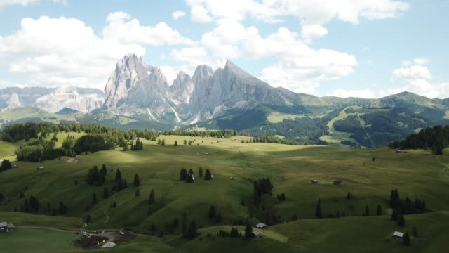 aerial view of the landscapes on alpe di siusi with sassolungo or langkofel mountain group in background and small cabins on grassland in summer, south tyrol, italy - langkofel stock videos & royalty-free footage