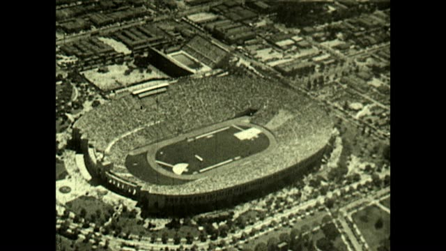 Aerial view of the Los Angeles Memorial Coliseum at the Olympic Games Opening Ceremony Reverse shot shows blimp and doves flying