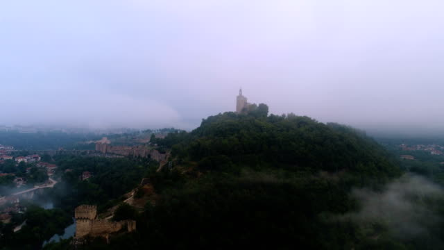 Aerial view of the morning mist covering a city with a winding riverbed passing along side and a tower on a hill popping up.