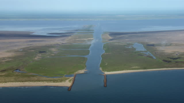 vidéos et rushes de aerial view of the mouth of port mansfield channel as it cuts through south padre island, on the gulf coast of texas. - gulf coast states