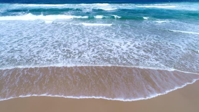 vídeos de stock e filmes b-roll de aerial view of the ocean and the sandy beach - cena de tranquilidade