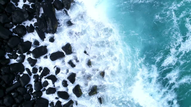 aerial view of the ocean waves hitting against the rocks - serenità video stock e b–roll