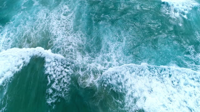 vídeos de stock e filmes b-roll de aerial view of the ocean waves splashing - câmara lenta