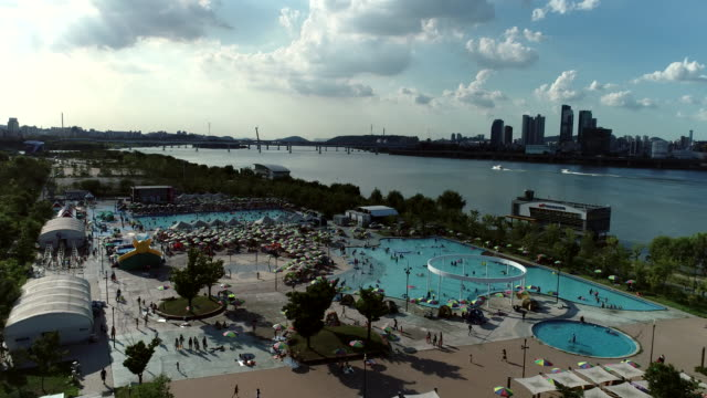 stockvideo's en b-roll-footage met aerial view of the outdoor swimming pool in ttukseom hangang park next to the han river in seoul, south korea - buitenbad