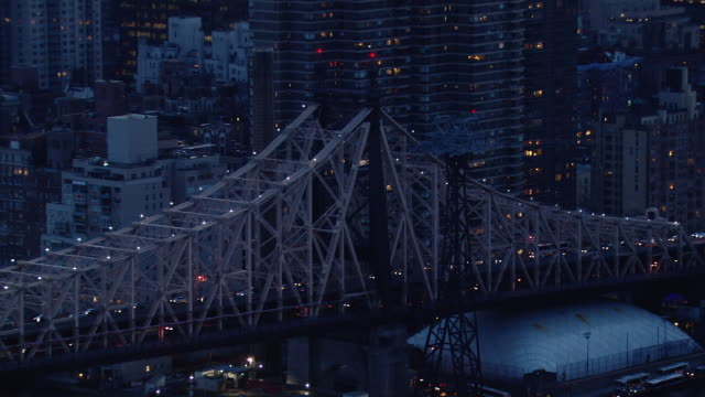 Aerial view of the Queensboro Bridge in New York City at dusk.
