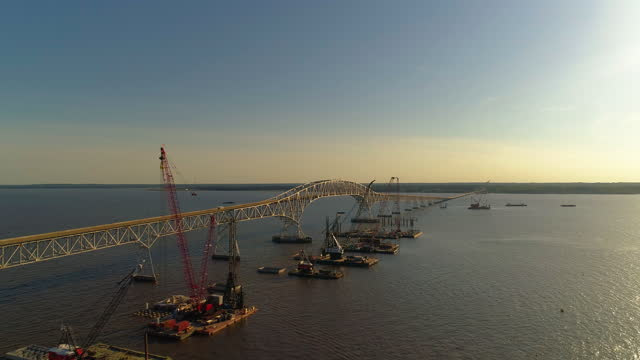 """aerial view of the reconstruction of the potomac river, near governor harry w. nice memorial/senator thomas """"mac"""" middleton bridge connected virginia and maryland, with multiple floating cranes vessels along with the construction site on the water. - virginia us state stock videos & royalty-free footage"""