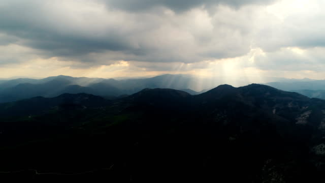 Aerial view of the Rhodopi mountains with sunbeams passing through the clouds