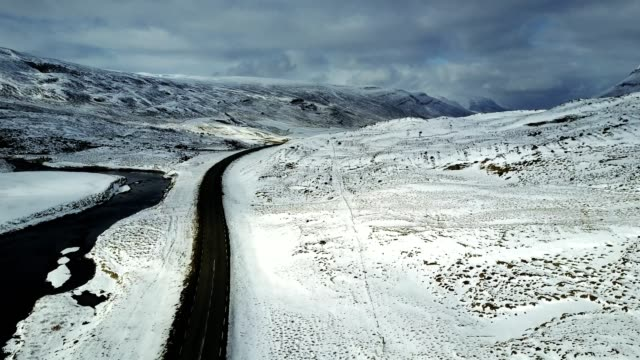 aerial view of the ring road in iceland with the snow background - ciglio della strada video stock e b–roll