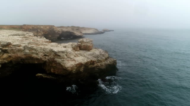 Aerial view of the rocky coastline in a fog