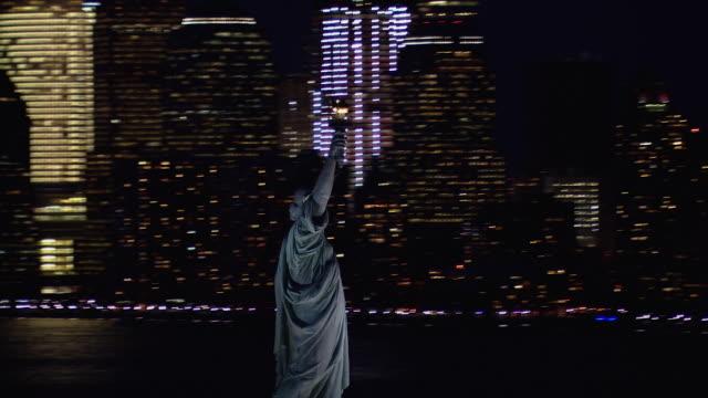 vídeos de stock, filmes e b-roll de aerial view of the statue of liberty and manhattan skyscrapers, illuminated at night. - estátua