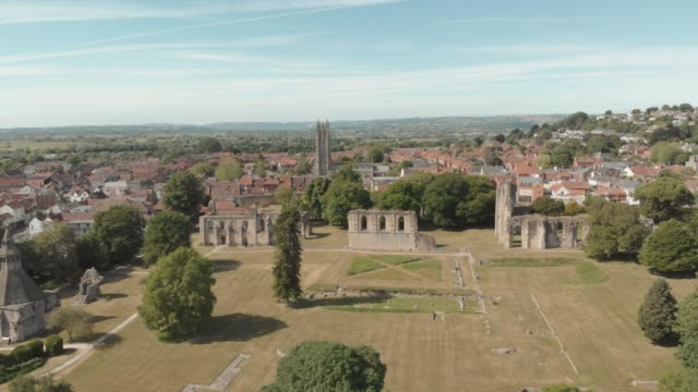 vídeos de stock e filmes b-roll de aerial view of the stone ruins of the 7thcentury ruins of bath abbey a grade i listed building and scheduled ancient monument in glastonbury somerset... - por volta do século 7 dc