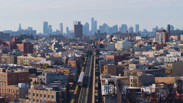 aerial view of the subway train passing on the elevated railroad in brooklyn, new york. aerial drone-made 4k uhd b-roll footage with the... - elevated train stock videos & royalty-free footage