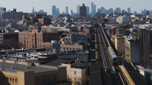 aerial view of the subway train passing on the elevated railroad in brooklyn, new york. aerial drone-made 4k uhd b-roll footage with the forward... - elevated train stock videos & royalty-free footage