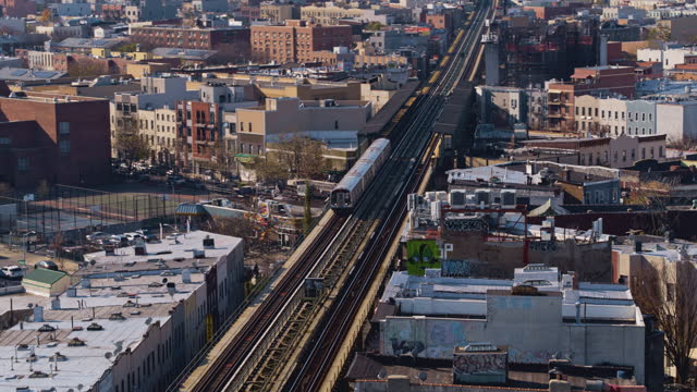 aerial view of the subway train passing on the elevated railroad in brooklyn, new york. 4k uhd b-roll footage with the backward-panning camera motion. - elevated train stock videos & royalty-free footage