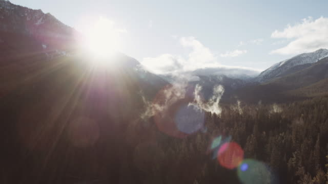 aerial view of the sun peaking around a mountain - biological process stock videos & royalty-free footage