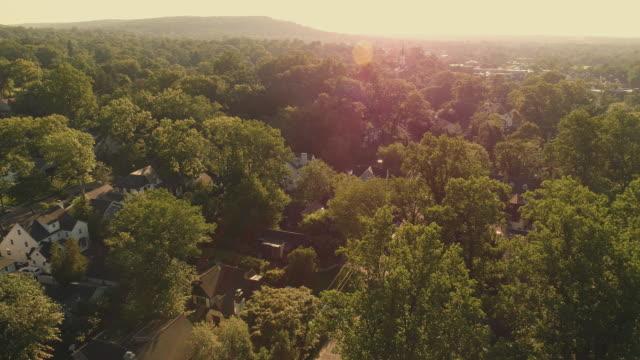 vidéos et rushes de vue aérienne du lever du soleil dans les zones suburbaines à millburn, new jersey, etats-unis. des séquences vidéo réalisées par drone avec le mouvement panoramique de la caméra. - quartier résidentiel