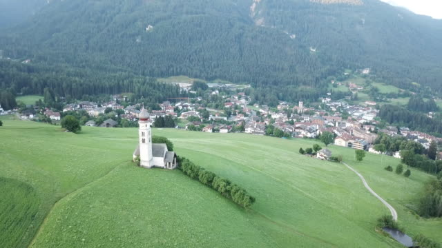 aerial view of the sunrise landscapes of church st. valentin on grassy hilltop in the valley of south tyrol, italy, europe - alpe di siusi video stock e b–roll