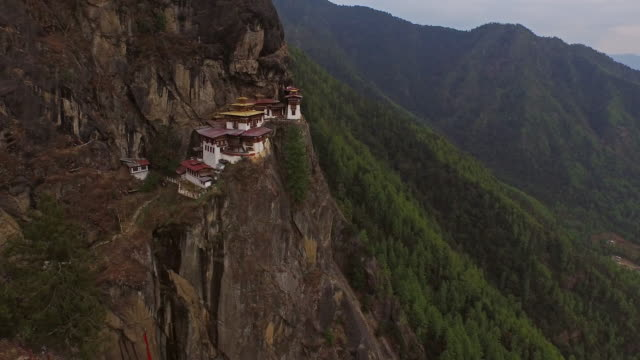 aerial view of the tigers nest monastery on the side of a cliff - bhutan stock videos & royalty-free footage