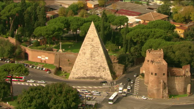 aerial view of the traffic around the pyramid of cestius and st. paul's gate / rome, italy - piramide struttura edile video stock e b–roll