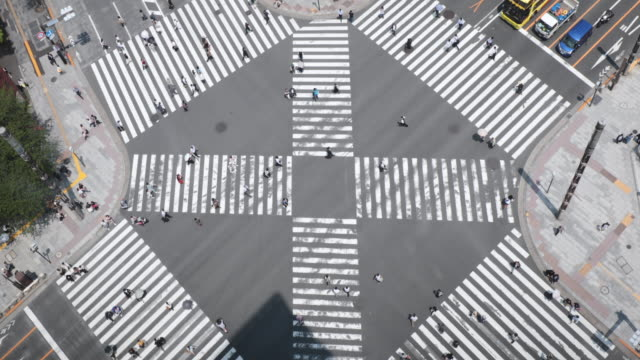 交差点のトラフィックの空中ビュー、道路を横切る人々 - 十字路点の映像素材/bロール