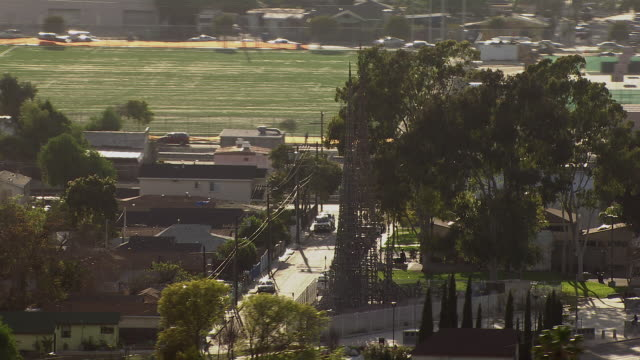 stockvideo's en b-roll-footage met aerial view of the watts towers and the simon rodia state historic park, located in the famous watts neighborhood of south los angeles. the sculpted towers are an important cultural landmark in a neighborhood known for its gangs and riots. - torenspits