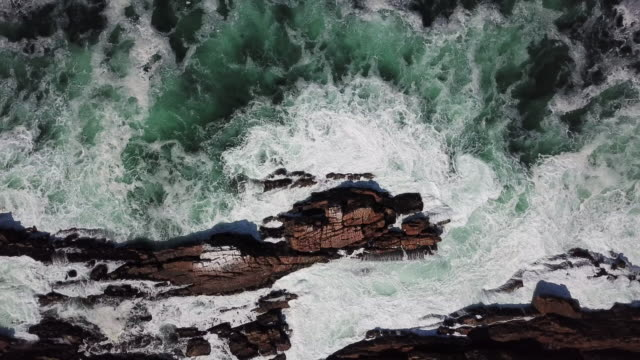 Aerial view of the waves crashing against the rocks