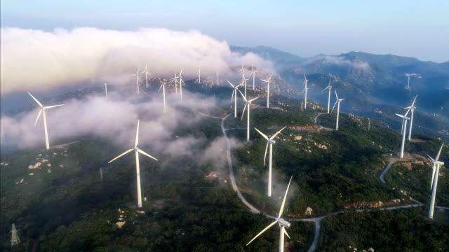 vídeos de stock, filmes e b-roll de vista aérea do moinho de vento no nevoeiro - turbina