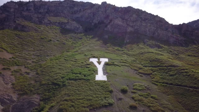 vídeos de stock e filmes b-roll de aerial view of the y on y mountain flying away from the hillside - provo