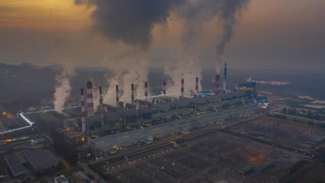 vidéos et rushes de vue aérienne de la centrale thermique ou centrale à charbon et tour de refroidissement avec de la vapeur dans la nuit au jour - synthpop