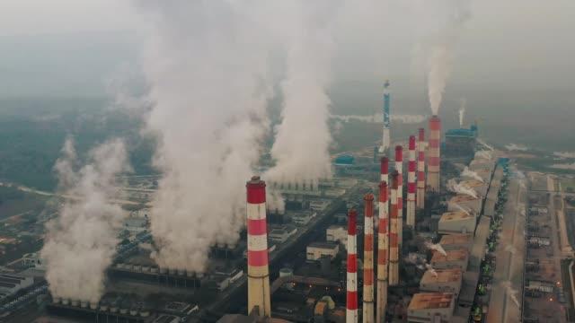 vidéos et rushes de vue aérienne de centrale thermique ou centrale de charbon et tour de refroidissement avec la vapeur la nuit au jour - synthpop