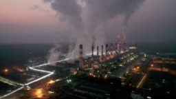 Aerial view of thermal power plant or coal power plant and cooling tower with steam at night to day