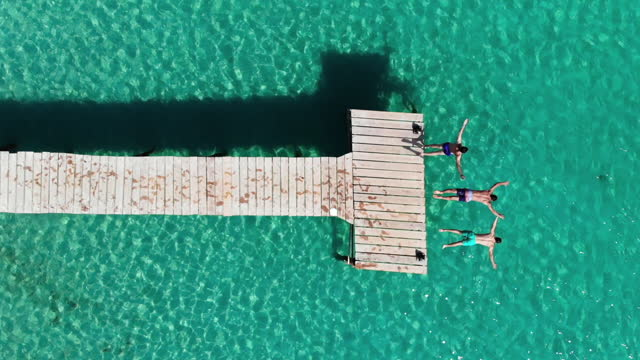 aerial view of three friends diving into the sea in mallorca island during summer. - jumping stock videos & royalty-free footage