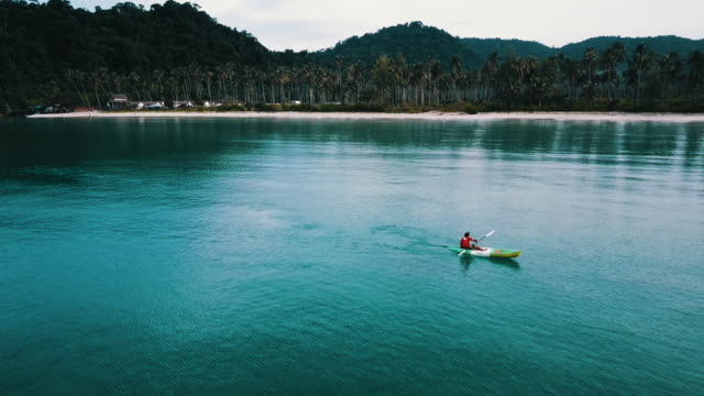 aerial view of tourist kayaking on in the sea. thailand. - turquoise coloured stock videos & royalty-free footage