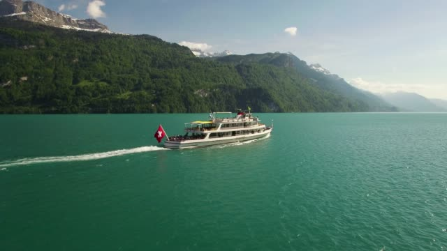 aerial view of tourist ship on lake with swiss flag in mountain range and alpine environment - schweiz stock-videos und b-roll-filmmaterial