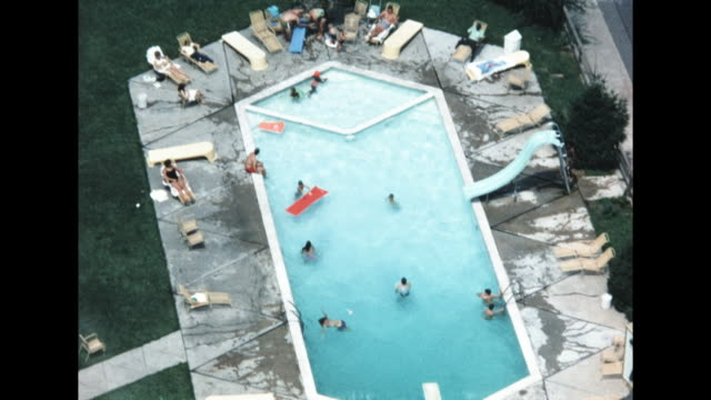 aerial view of tourists swimming and using a waterslide in a motel pool - water slide stock videos & royalty-free footage