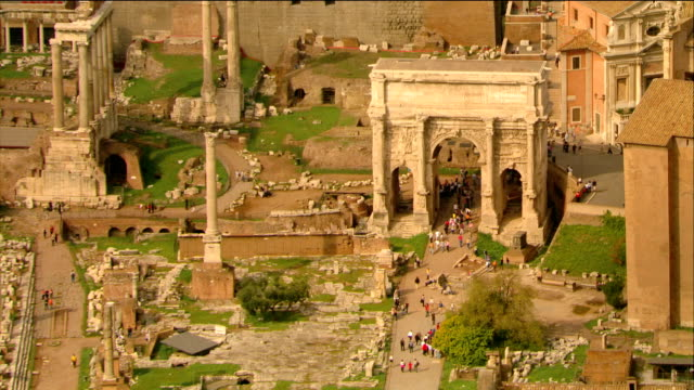 Aerial view of tourists walking near Arch of Septimius Severus / zoom out view of the Roman Forum / Rome