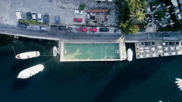 Luftaufnahme der Stadt an der Küste gelegen. Hafen und Fußball Gericht