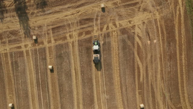 aerial view of tractor collecting hay and releasing hay rolls on field - tractor stock videos & royalty-free footage