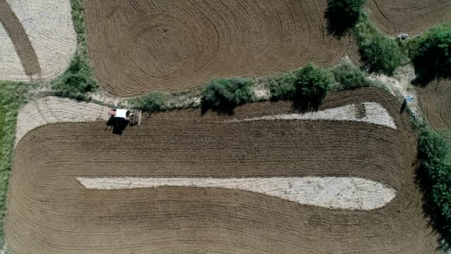 aerial view of tractor ploughing fields - punjab pakistan stock videos and b-roll footage