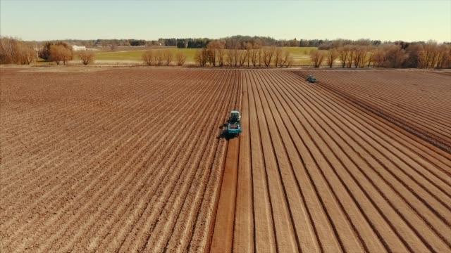 vidéos et rushes de vue aérienne du labour de tracteur au champ de pomme de terre - pomme de terre