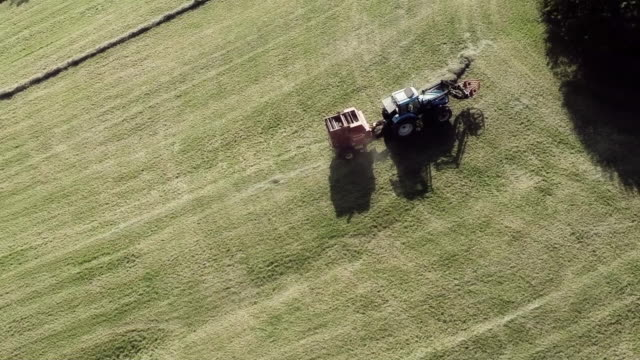 aerial view of tractor with straw baler on harvested field - hay baler stock videos & royalty-free footage