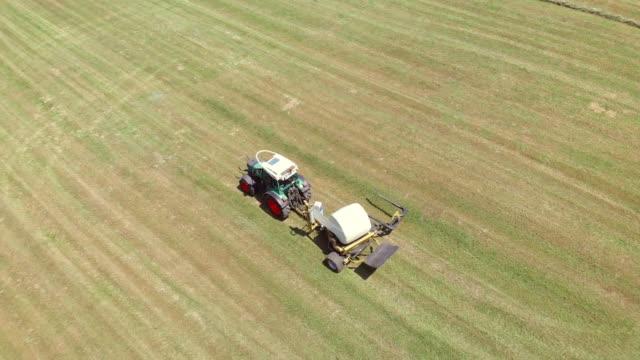 luftaufnahme eines traktors, der einen heuballen in kunststoff wickelt - cereal plant stock-videos und b-roll-filmmaterial